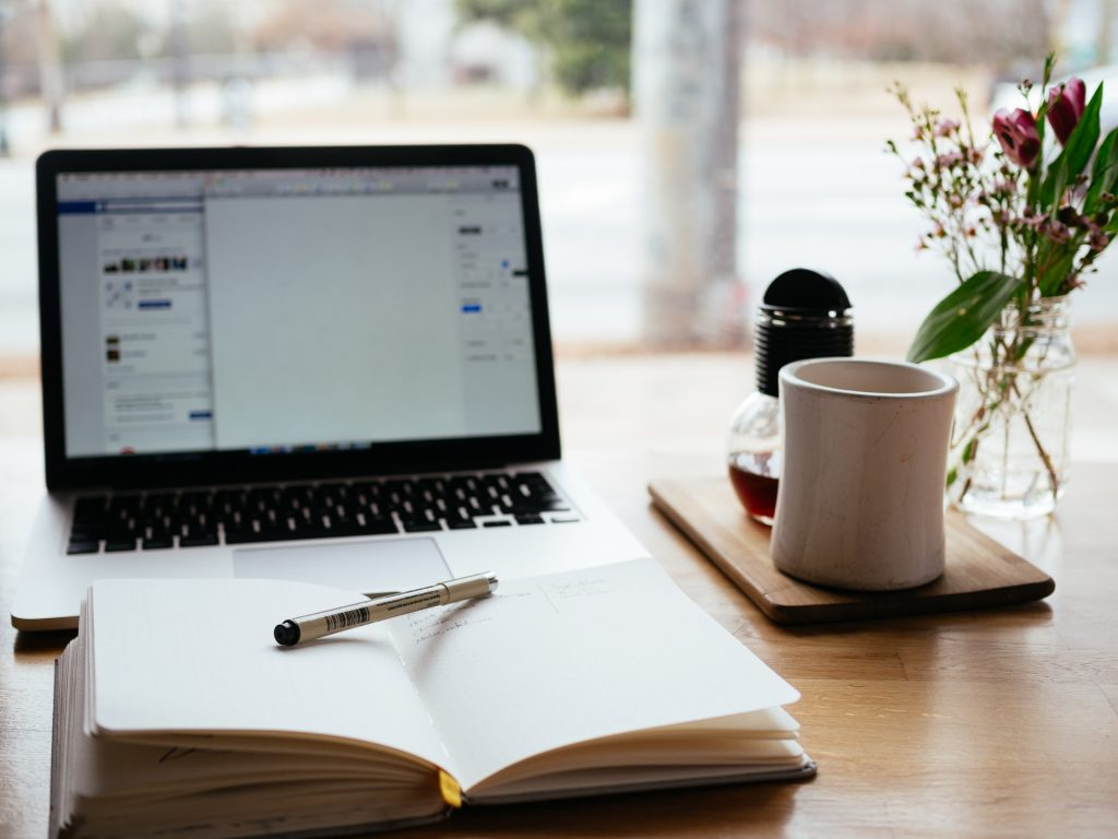 Image of laptop with Bible and pencil shown that help write articles